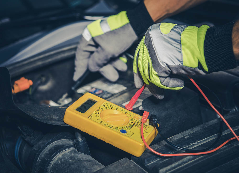 Car electrician checks the battery level
